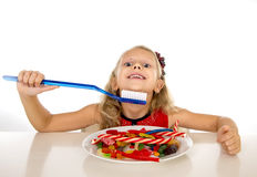 Cute female child eating dish full of sweets and holding huge toothbrush in dental care and health concept Royalty Free Stock Photo