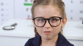 Cute female child in eyeglasses eating carrot, vision care beta-carotene vitamin. Stock footage stock video