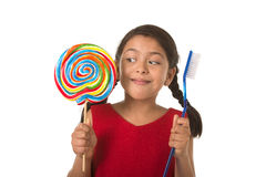 Cute female child holding big spiral lollipop candy and huge too Stock Images