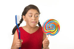 Cute female child holding big spiral lollipop candy and huge too Royalty Free Stock Photo