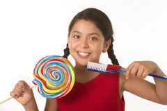 Cute female child holding big spiral lollipop candy and huge toothbrush in dental care concept. Cute female child holding big spiral lollipop candy and huge Royalty Free Stock Photos