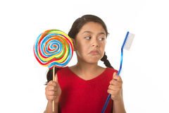 Cute female child holding big spiral lollipop candy and huge toothbrush in dental care concept Royalty Free Stock Photography