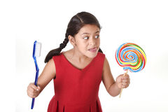Cute female child holding big spiral lollipop candy and huge toothbrush in dental care concept Stock Photo