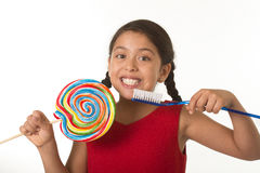 Cute female child holding big spiral lollipop candy and huge toothbrush in dental care concept Stock Image