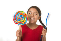 Cute female child holding big spiral lollipop candy and huge toothbrush in dental care concept Stock Photos