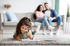 Cute Female Child Resting On Floor At Home And Drawing With Pencils. While Her Parents Relaxing On Couch With Digital Tablet, Happy Arab Family Enjoying