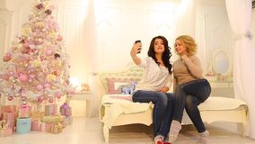 Cute female friends photographed on camera smartphone, sitting on bed in bright bedroom with festive Christmas tree on. Adorable girls do selfie on front camera stock video footage
