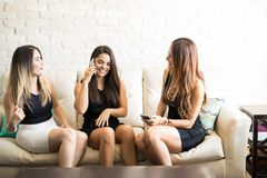 Girls making plans for the night. Cute female friends and roomies getting ready to go out at night and making plans on the phone Royalty Free Stock Photography