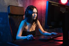 A cute female gamer girl sits in a cozy room behind a computer and plays games. Woman live streaming computer video. Games to her fans. Streamer and gamer royalty free stock photo