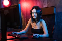 A cute female gamer girl sits in a cozy room behind a computer and plays games. Woman live streaming computer video. Games to her fans. Streamer and gamer stock photography