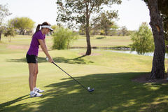 Cute female golfer teeing off Royalty Free Stock Photos