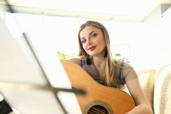 Cute Female Guitarist Instrument Playing Tutorial. Beautiful Woman Learning Musical Art at Home. Musician Person Looking at Notes on Music Stand. Stunning royalty free stock images
