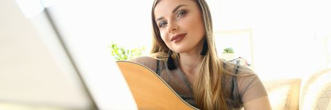 Cute Female Guitarist Instrument Playing Tutorial. Beautiful Woman Learning Musical Art at Home. Musician Person Looking at Notes on Music Stand. Stunning royalty free stock photo