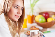 Cute female having morning coffee. Portrait of cute blond female having coffee in the kitchen, enjoying happy lazy morning, peace and relaxation at home Royalty Free Stock Photo