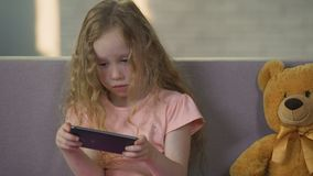 Cute female kid enjoying game on smartphone, gadget addiction, childhood. Stock footage stock video footage