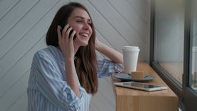 Female talking on a mobile phone. Cute female laughing and enjoying talking on the smartphone, active smiling girl talk on a mobile phone stock video