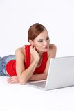 Cute female lying down and using a laptop Stock Photo