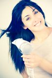 Cute female model blow drying long silky black hair Royalty Free Stock Photography