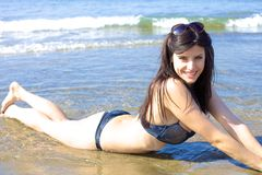 Cute female model smiling happy laying on seaside Royalty Free Stock Image