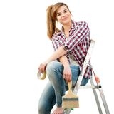 Cute female painter sitting on ladder. Royalty Free Stock Images