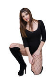 Cute female posing in the studio dressed in sexy bodysuit. Cute female kneeling, hand on legs, open legs in studio dressed in sexy bodysuit, black fishnet holes Stock Photo
