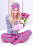 Cute female receive gift. Portrait of happy cute female sitting on the bed in the morning and curiously open little gift box which receive in Valentine day Stock Images