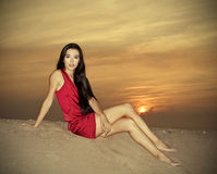 Cute female in red dress posing at the desert in sunset Royalty Free Stock Image
