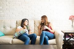 Roomates drinking some coffee. Cute female roomates relaxing at home and drinking coffee together Royalty Free Stock Photography