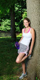Cute female runner pauses under a tree to drink Royalty Free Stock Photography