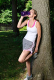 Cute female runner pauses under a tree to drink Royalty Free Stock Photo