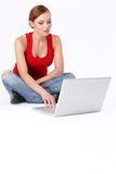Cute female sitting and using a laptop Royalty Free Stock Photo