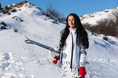 Cute female skier holding ski equipment. Cute grinning young adult female in long dark hair standing with skis, red gloves and helmet in the front of hill with Royalty Free Stock Photos