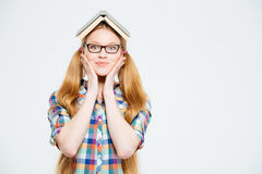 Cute female student with book on head Royalty Free Stock Images
