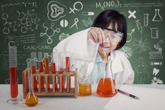 Cute female student doing chemical test. Cute female elementary school student doing chemical test while wearing coat in the lab Royalty Free Stock Image