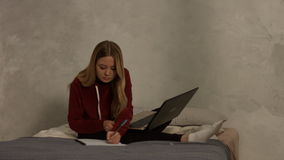 Cute female student with laptop studying in bedroom stock video footage