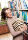 Cute female student in a library. Cute female student holding a stack of books Royalty Free Stock Photos