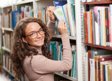Cute female student in a library. Cute female student looking for materials in the library Stock Photo