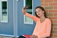Cute female student taking photo of self Stock Images