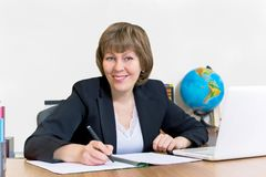 Cute female teacher working at table royalty free stock photography