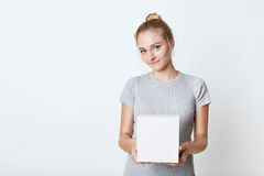 Cute female teenager with hair knot, wearing t-shirt, holding white box in hands, preparing surprise for her mother. Adorable fema Stock Photography