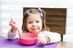 Preschool Girl Eating Food At Home. Cute female toddler smiling while having noodles at dining table royalty free stock photo