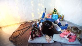 Cute female and two little girls children, posing for camera and smiling, lying on cushions, on floor in room with. Adorable little girls and young woman elder stock video