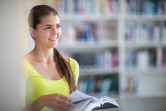 Cute female university/highschool student in library. Cute female university/highschool student with books in library royalty free stock images