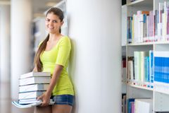 Cute female university/highschool student in library. Cute female university/highschool student with books in library royalty free stock photography
