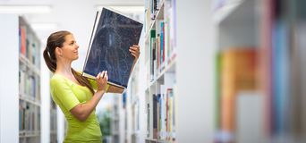 Cute female university/highschool student in library. Cute female university/highschool student with books in library royalty free stock photo