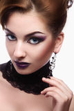 Cute female with violet make up looking at camera on white backg Stock Photo