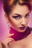 Cute female with violet make up looking at camera on white backg Royalty Free Stock Image