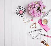 Cute feminine accessories and pink flowers on the table Royalty Free Stock Photos
