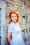 Cute fiery red-haired gray-blue eyes girl standing by the brick wall stock photography