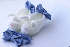Cute first white baby booties with bows and little blue bow tie royalty free stock photography